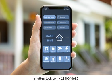 female hand holding phone with app smart home on screen background of the house