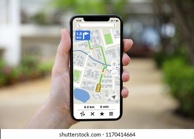female hand holding phone with app navigation map on screen nature background