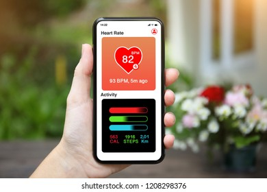 female hand holding phone with app heart and activity screen on background of house with flower garden