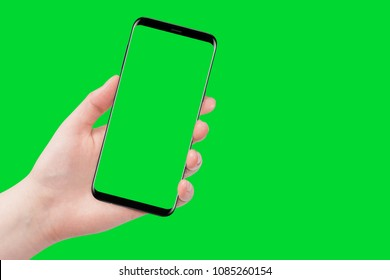 Female hand holding phone, isolated on green background