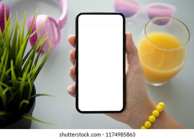 female hand holding phone with isolated screen above table with headphones glasses and juice