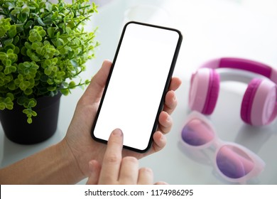 female hand holding phone with isolated screen above table with headphones and glasses
