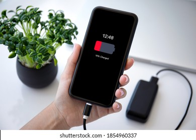 female hand holding phone with red discharged battery on screen connected to powerbank