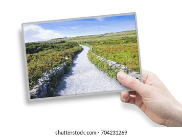 A female hand holding an postcard about a typical Irish flat landscape in Aran Island with country road, stone walls and fields of grass for grazing animals (Ireland).