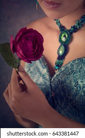 Female hand holding purple artificial rose