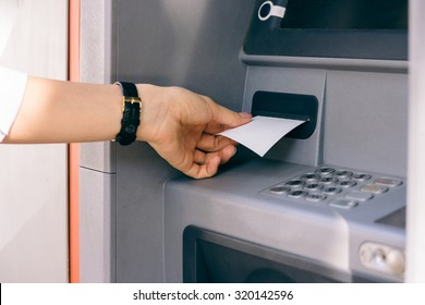 Female hand holding a receipt obtained from the ATM after withdrawing cash. The outer bank terminal.