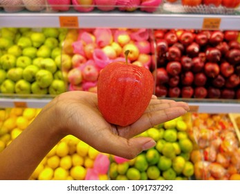 Female hand holding red apple in supermarket.