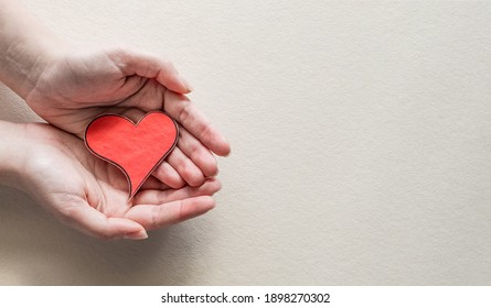 Female hand holding red heart. Organ donation, family insurance. World heart day, World health day, Gratitude, be kind, be thankful. Love concept.
