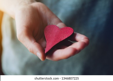 female hand holding red wooden heart, love, care concept, blood donation, world heart day, heart health