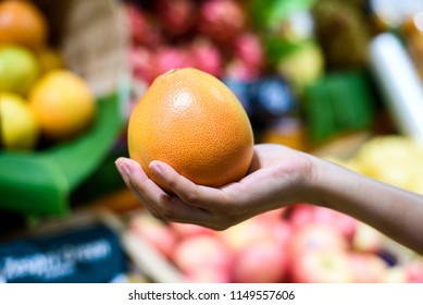 Female Hand holding selected Orange in fruits market