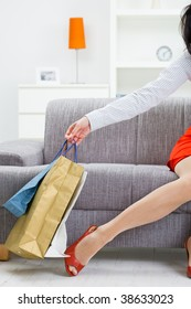 Female hand holding shopping bags, leg in stocking and red shoes.