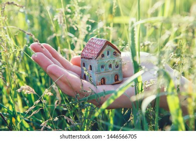 female hand holding small house, real estate, home protection and safety concept, natural background