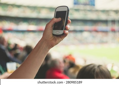A female hand is holding a smart phone in a stadium to take pictures of a sporting event