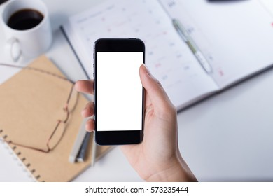 A female hand holding smart phone with office stationeries at working desk.