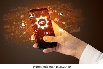 Female hand holding smartphone with ADS abbreviation, modern technology concept