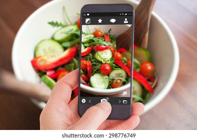 Female hand holding a smartphone against close up of a fresh salad