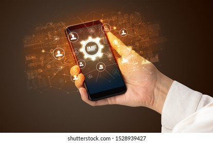 Female hand holding smartphone with IMF abbreviation, modern technology concept