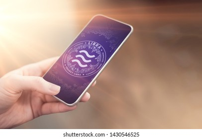 Female hand holding smartphone with new independent cryptocurrency - Libra, and some made up interface around it. New on-line payments with smartphone concept - Image