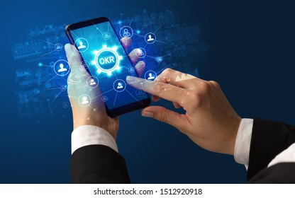 Female hand holding smartphone with OKR abbreviation, modern technology concept