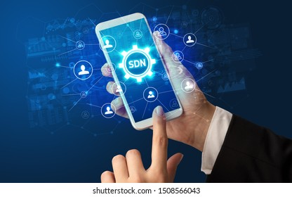 Female hand holding smartphone with SDN abbreviation, modern technology concept