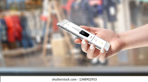 Female hand holding smartphone and shopping online, fashion store in background
