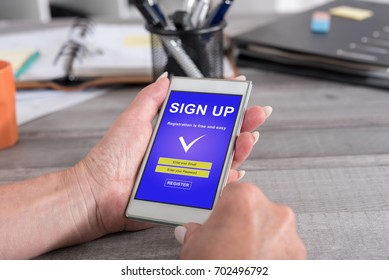 Female hand holding a smartphone with sign up concept
