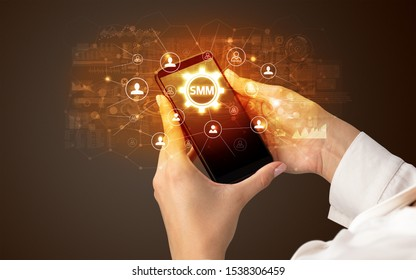 Female hand holding smartphone with SMM abbreviation, modern technology concept