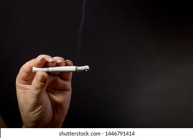 Female hand holding a smoldering cigarette on a black background