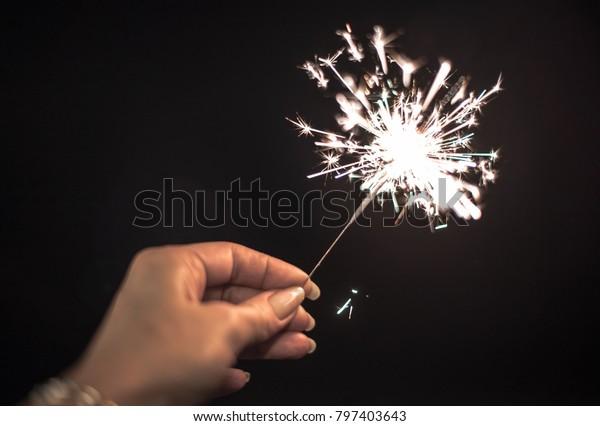 Female hand holding sparkler or Bengal lights.