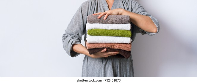 female hand holding stack clean bath towels colorful cotton terry textile background closeup