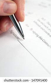 A female hand holding a stylish pen over a contract about to be signed.