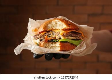 Female hand holding tasty bitten burger on color background