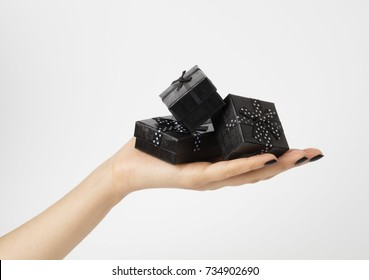 Female hand holding a three black gift-boxes on a palm. Isolated on white background. Shallow depth photo