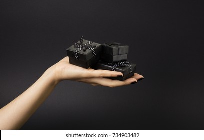 Female hand holding a three black gift boxes on a palm. Isolated on black background. Shallow depth photo