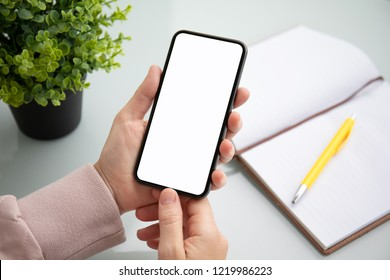 female hand holding touch phone with isolated screen above the table in the office