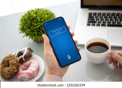 female hand holding touch phone with app personal assistant on screen above the table in cafe