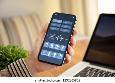 female hand holding touch phone with app smart home on screen above the table with laptop