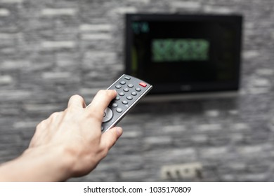 Female hand holding tv remote control and changing channel pushing a button