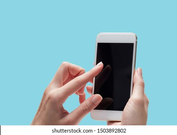 female hand holding using smart phone on bright blue background. copy space for text
