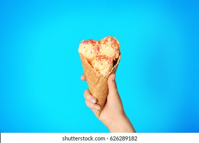 Female hand holding waffle cone with delicious ice cream on blue background