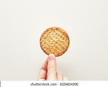 Female hand holding wheat cracker isolated on white background