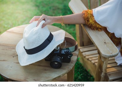 Female hand holding a white hat with a camera placed. On holiday and nature around.