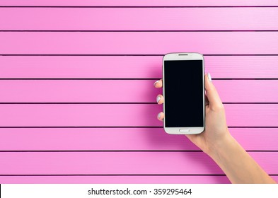 Female hand holding white mobile phone over pink background