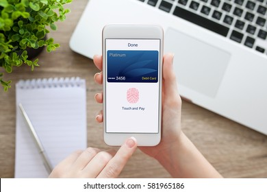 female hand holding white phone with debit card and app touch pay near laptop