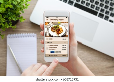 female hand holding white phone with app delivery food screen and laptop