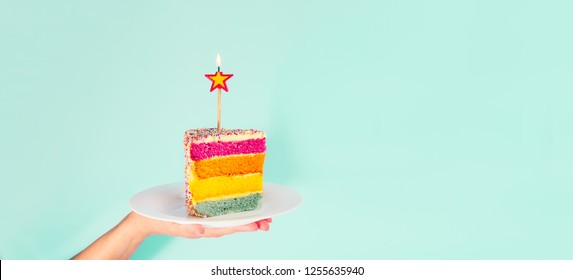 Female hand holding white plate with slice of Rainbow cake with birning candle in the shape of star isolated on blue background. Happy bithday, party concept. Wide banner. Selective focus. Copy space