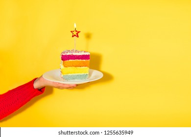 Female hand holding white plate with slice of Rainbow cake with birning candle in the shape of star isolated on yellow background. Happy bithday, party concept. Selective focus. Copy space