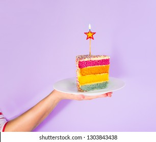 Female hand holding white plate with slice of Rainbow cake with birning candle in the shape of star isolated on blue background. Happy bithday, party concept. Square card. Selective focus. Copy space