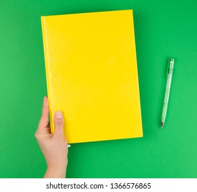 female hand holding a yellow closed notebook and pen on a green background, top view