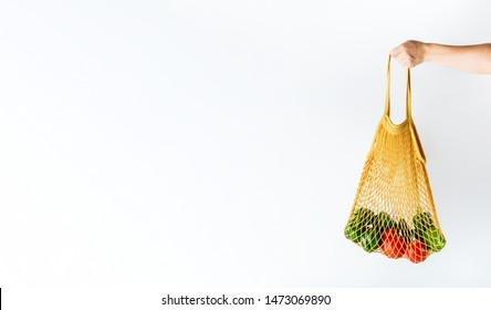 Female hand holding a yellow mesh bag with vegetables on white background with copy space. Zero waste shopping concept.